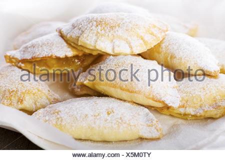 Délicieux biscuits sur la plaque avec du papier blanc Banque D'Images
