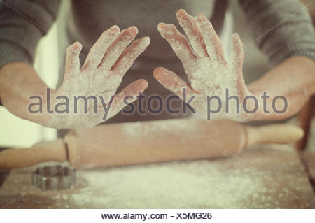 Femme avec la farine sur les mains à l'aide de rouleau à pâtisserie Banque D'Images