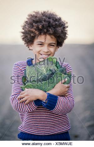 Portrait of boy hugging champ dans le chou Banque D'Images