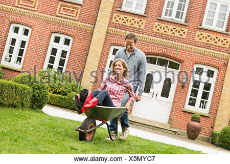 Mid adult man pushing woman in brouette