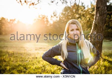Portrait of young woman in sunlit park Banque D'Images