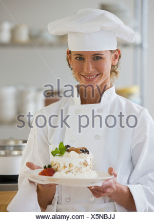 Femme chef holding plate of dessert Banque D'Images