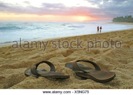 Coucher de soleil sur la plage de sable fin sur Oahu's northshore comme ce slipper propriétaire choisit de marcher pieds nus Banque D'Images