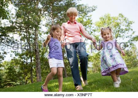 Grand-mère et petites-filles holding hands Banque D'Images