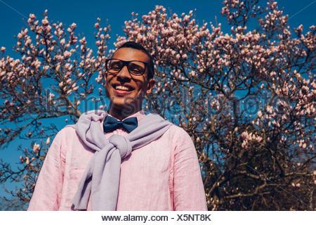 Jeune homme dans le parc au printemps, portant nœud papillon Banque D'Images
