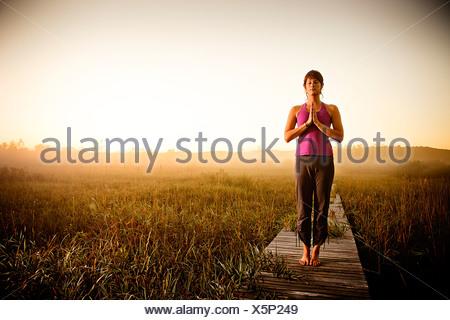 Mid adult woman doing yoga matin dans un champ, la Réserve Naturelle du Lac de hareng, Francfort, Benzie County, Michigan, USA Banque D'Images