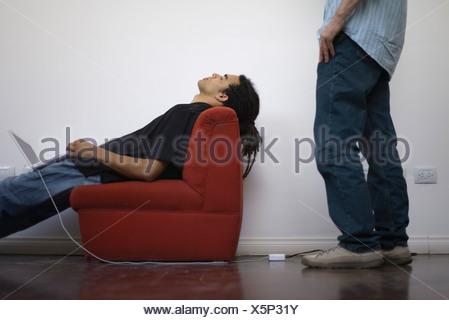 Homme sieste dans un fauteuil avec ordinateur portable en équilibre sur tour, collègue debout derrière regarder Banque D'Images
