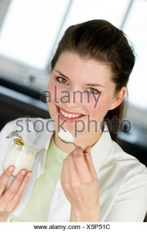 Portrait d'une jeune femme souriante de manger un yogourt nature Banque D'Images