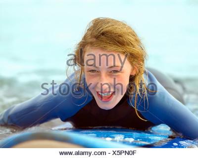 Les femmes sur la prise de petite vague de surf Banque D'Images