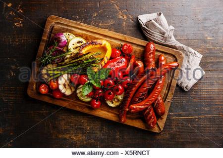 Saucisses grillées et de légumes sur une planche à découper sur fond de bois foncé Banque D'Images