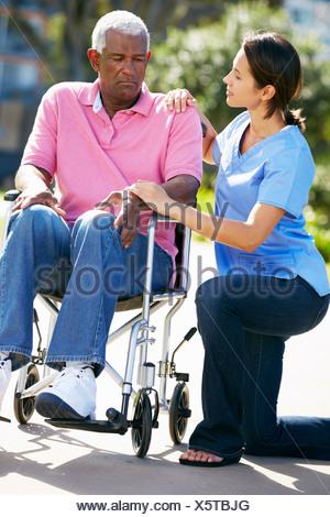 Carer poussant malheureux Senior Man In Wheelchair Banque D'Images