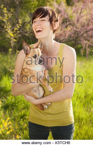 Jeune femme dans les champs au printemps tenant un chien Banque D'Images