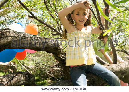 Young Girl sitting in tree at Birthday party Banque D'Images