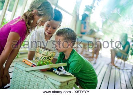Les jeunes enfants à la recherche de graines dans un pot du semoir Banque D'Images