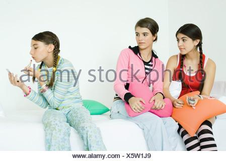 Trois jeunes amis féminins assis sur un canapé, deux regardant plus jeune fille en mettant sur le maquillage Banque D'Images