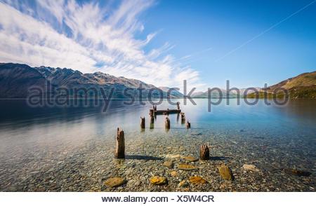 Jetée de pourri, vieux poteaux de bois dans le lac Wakatipu à Glenorchy, Région de l'Otago, Southland, Nouvelle-Zélande Banque D'Images