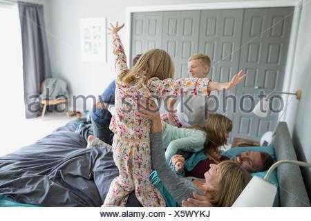 Enfants ludique en pyjama de sauter sur les parents au lit Banque D'Images