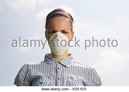Une jeune femme portant un masque de la pollution Banque D'Images