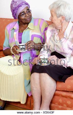 Deux femmes âgées assis sur un canapé de parler et de boire le thé Banque D'Images