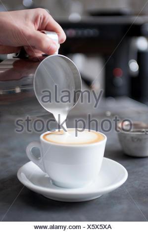 Verser le lait à la vapeur pour cappuccino Banque D'Images