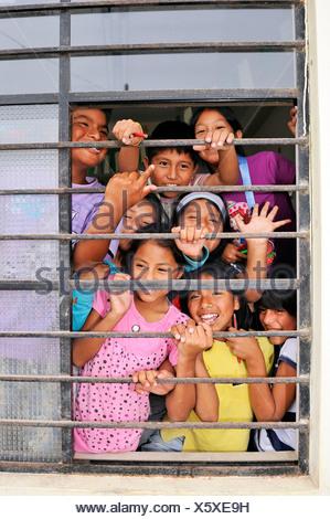 Les enfants rient derrière la fenêtre d'une école, quartier pauvre de Villa El Salvador, Lima, Pérou, Amérique du Sud Banque D'Images