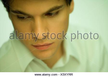 Jeune homme regardant vers le bas, portrait Banque D'Images