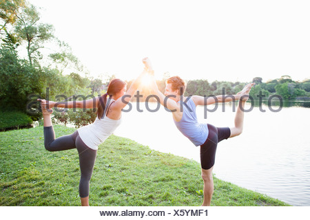Couple practicing yoga par l'eau Banque D'Images