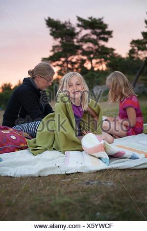 La Suède, Gotland, Faro, Girl (10-11) sitting on picnic blanket avec mère et sa sœur (8-9) Banque D'Images