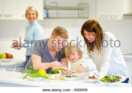 Famille dans la cuisine. Trois générations. L'alimentation saine. Une croissance saine. Faire une salade de légumes. Banque D'Images