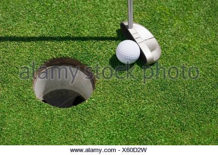 Balle de golf près de cup le putting green en plein air Banque D'Images