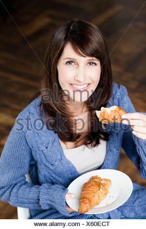 Woman eating croissant Banque D'Images