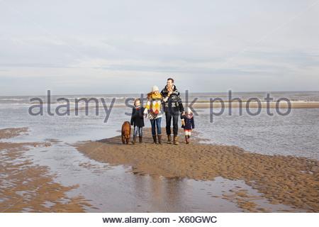 Mid adult parents avec son fils, sa fille et le chien se promener sur la plage, Bloemendaal aan Zee, Pays-Bas Banque D'Images