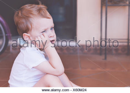 Boy sitting on floor with hand on chin Banque D'Images
