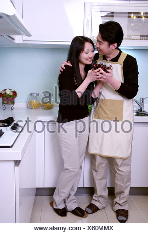 Couple holding bowl of cherries in kitchen Banque D'Images