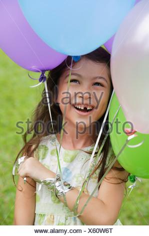 Jeune fille avec plusieurs ballons, smiling Banque D'Images