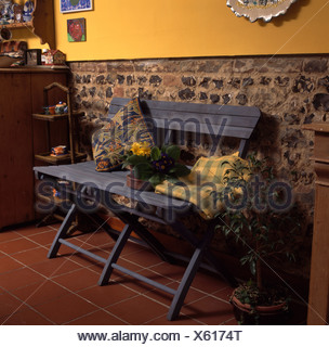 Tapis jaune vérifié sur banc en bois peint en bleu contre le mur en pierres apparentes dans la salle jaune Banque D'Images