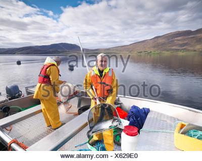 Fisherman holding salmon dans net Banque D'Images