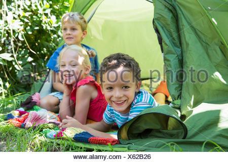 Portrait de trois enfants souriants couché dans la tente de jardin Banque D'Images