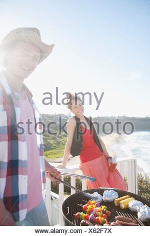 L'homme et la femme ayant tendance barbecue avec ocean in background Banque D'Images