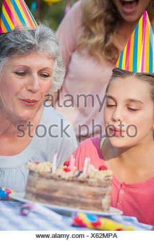 Close up de jeune fille et sa grand-mère blowing candles Banque D'Images
