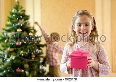 Portrait of Girl (4-6) avec boîte cadeau rose, frère (7-9) hanging décoration d'arbre de Noël en arrière-plan Banque D'Images