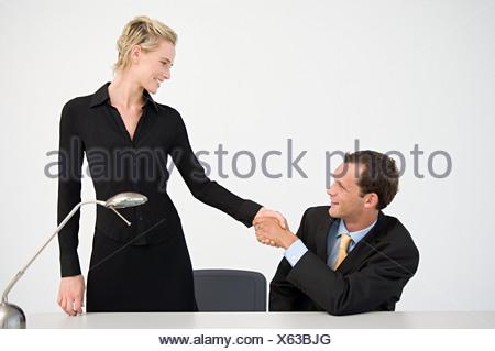 Poignée de main entre deux employés de bureau