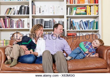 Les parents et les jeunes adultes milieu fils s'amusant sur canapé Banque D'Images
