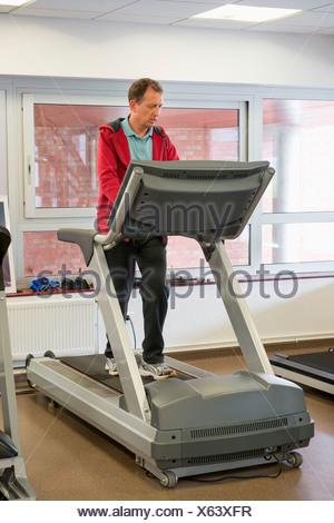 Homme qui court sur un tapis roulant dans une salle de sport Banque D'Images