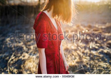 La Finlande, les jeunes World, cheveux rouge femme en robe rouge debout dans la lumière du soleil Banque D'Images
