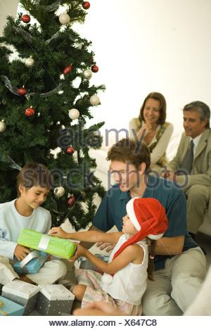 Le père et les deux enfants assis par arbre de Noël, l'ouverture présente ensemble, les adultes en arrière-plan Banque D'Images