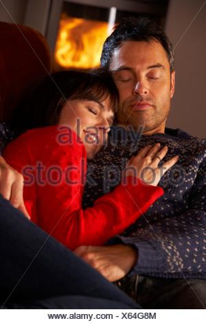 Couple d'âge moyen de câlins sur canapé par Cheminée Banque D'Images