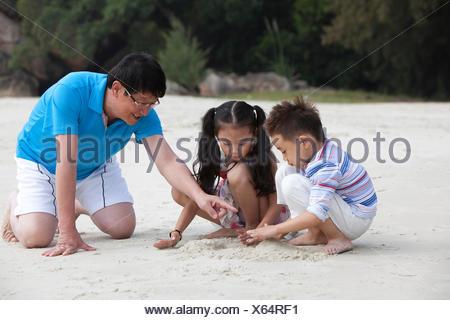 Les grands-parents et petits-enfants jouant dans la station balnéaire Banque D'Images