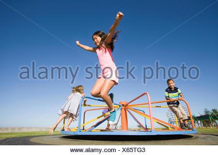 Les enfants sautant hors manège à jeux pour enfants Banque D'Images