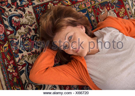 Portrait of senior woman lying on floor, Munich, Bavière, Allemagne Banque D'Images